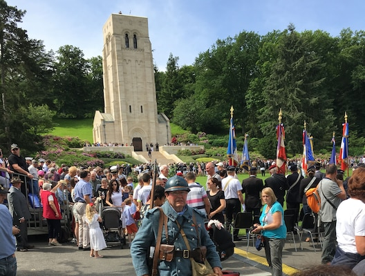 A reenactor joins attendees in honoring the sacrifices of Allied forces 100 years ago during the battles of Belleau Wood and Château-Thierry in France, near the end of World War I. In the background is the Aisne-Marne Memorial.