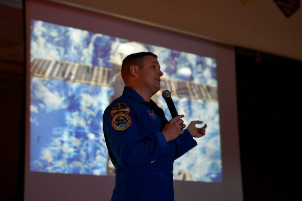 "Col. Jack ""2 Fish"" Fischer, NASA astronaut, gives a presentation in front of a projector screen playing footage from his missions, May 22, 2018, at Aurora Quest K-8 School, Aurora, Colorado. Fischer's speech was a surprise for nearly 600 students at Aurora Quest K-8 School, who thought they would be attending a general assembly. (U.S. Air Force photo by Senior Airman Madison J. Ratley)"