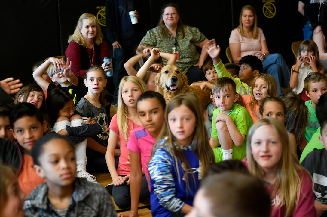"Children and dog listen to special guest speaker Col. Jack ""2 Fish"" Fischer, NASA astronaut, speak about his personal experiences in space exploration, May 22, 2018, at Aurora Quest K-8 School, Aurora, Colorado. The presentation was held during a general assembly and was a surprise to the nearly 600 students in attendance. (U.S. Air Force photo by Senior Airman Madison J. Ratley)"