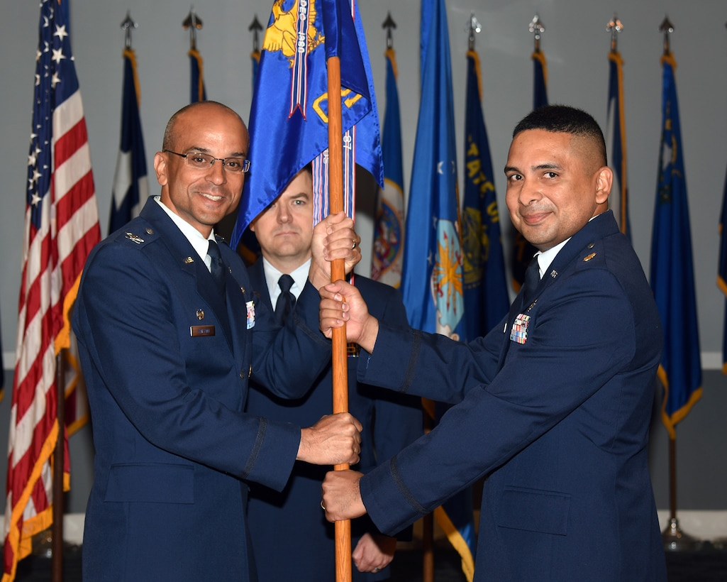 Col. Anthony Sansano, 14th Mission Support Group commander, passes the 14th Communications Squadron guidon to Maj. Eddy Gutierrez, the new 14th CS commander, May 30, 2018, on Columbus Air Force Base, Mississippi. Gutierrez's last assignment was at Barksdale AFB, Louisiana. (U.S. Air Force photo Sharon Ybarra)