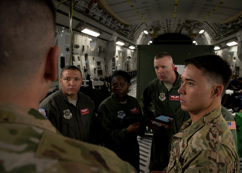 Tech. Sgt. John Brenden, 21st Airlift Squadron loadmaster, briefs aeromedics from the 375th Aeromedical Evacuation Squadron and Capt. Kai Yamashiro, 21st AS C-17 Globemaster III pilot, on egress procedures and his load plan at Travis Air Force Base, Calif., May 13, 2018. A 21st AS C-17 embarked on an AE mission supporting aerial transport of patients at various military bases in the Pacific. (U.S. Air Force photo by Lan Kim)