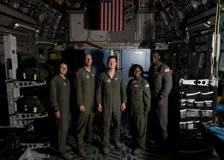 Airmen with the 375th Aeromedical Evacuation Squadron and 18th AES pause during a flight for a group photo on board a C-17 Globemaster III from Travis Air Force Base, Calif., May 14, 2018. The AE team along with a 21st Airlift Squadron C-17 aircrew and 860th Aircraft Maintenance Squadron flying crew chiefs departed Joint Base Pearl Harbor-Hickam, Hawaii, in support of the aerial transport of patients at various military bases in the Pacific. (U.S. Air Force photo by Lan Kim)