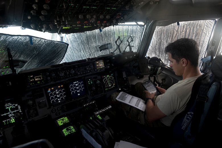 Lt. Col. Corey Akiyama, 21st Airlift Squadron C-17 Globemaster III pilot, loads a flight plan inside the cockpit before departing Anderson Air Force Base, Guam, May 16, 2018. A 21st AS C-17 aircrew, 860th Aircraft Maintenance Squadron flying crew chiefs and aeromedics with the 375th AES and 18th AES departed Anderson AFB in support of the aerial transport of patients at various military bases in the Pacific. (U.S. Air Force photo by Lan Kim)