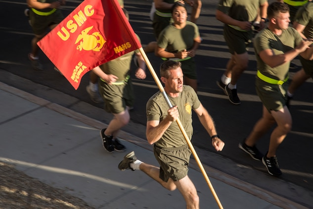 U.S. Marine Corps Maj. Jonathan D. Schaafsma, executive officer of Headquarters and Headquarters Squadron (H&HS), Marine Corps Air Station (MCAS) Yuma, Ariz., runs with the squadron guidon during a motivational run on MCAS Yuma, Ariz., May 25, 2018. H&HS conducted the motivational run to kick off the Memorial Day 96 hour liberty period, and to say farewell to Lt. Col. James S. Tanis. Lt. Col. Tanis served as the commanding officer of H&HS  for the past two years. (U.S. Marine Corps photo by Sgt. Allison Lotz)