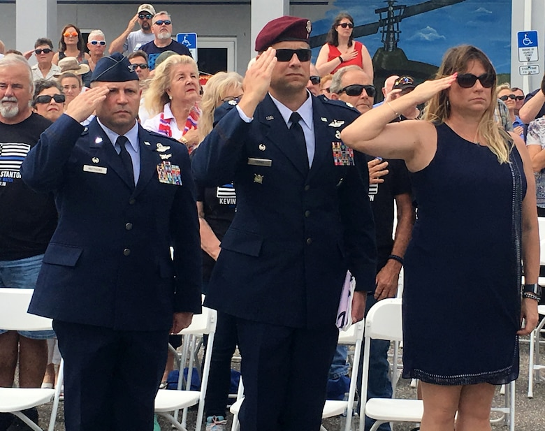 A year-and-a-half into commanding the 920th Rescue Wing and Col. Kurt A. Matthews, shown left, is getting ready to attend his fourth burial. The tragedy of the past year brought Memorial Day 2018 into perspective for 2,000 Reserve Citizen Airmen that serve with the 920th RQW. Matthews honored the lives of four wing members who were lost within the past year, two who were killed in combat March 15, 2018, MSgt. Bill Posch and SSgt. Carl Enis. During the event at the Brevard Veterans Center, Matthews, left; Lt. Col. Tim Hanks, shown center, 308th Rescue Squadron commander, and Hank's wife, Heather Hanks, render a salute to honor the ultimate sacrifice of 308th members Posch and Enis. (U.S. Air Force photo by Mr. Darrell Hankins)
