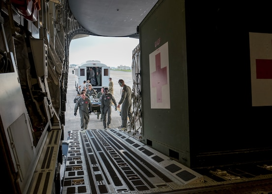 An aeromedical evacuation and critical care air transport team consisting of Airmen from the 375th AE Squadron, 18th AE Squadron, 673rd Medical Group, 36th Medical Group and 124th Medical Group, load a priority care patient onto a C-17 Globemaster III at Kadena Air Base, Japan, May 17, 2018. The C-17 from Travis AFB, Calif., was configured by an AE aircrew to provide aerial transport of patients throughout the Pacific region. (U.S. Air Force photo by Lan Kim)