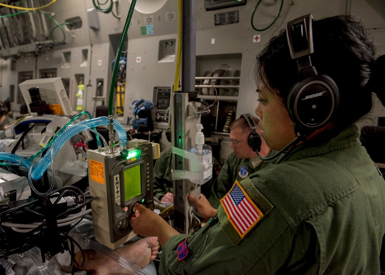 U.S. Air Force Master Sgt. Virginia Holmgren, a 124th Medical Group respiratory therapist with the Idaho Air National Guard, adjusts a patient's ventilation levels on board a C-17 Globemaster III from Travis Air Force Base, Calif., after leaving Joint Base Pearl Harbor-Hickam, Hawaii, May 18, 2018. Holmgren was part of a critical care air transport team providing medical supervision of a patient back to Travis. (U.S. Air Force photo by Lan Kim)