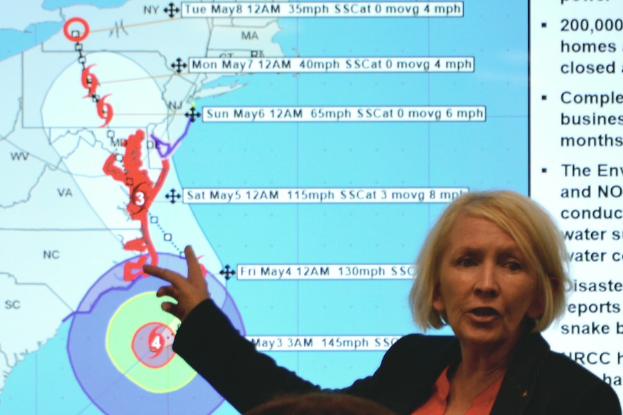 A woman points to a map showing the track of a simulated hurricane.