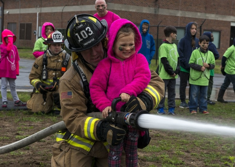 A firefighter assigned to the 103rd Airlift Wing helps a young girl spray a fire hose May 19, 2018.