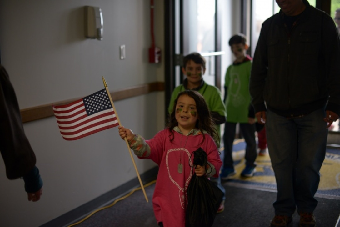 A child of a Connecticut National Guardsman waves an American Flag after returning from a simulated deployment May 19, 2018