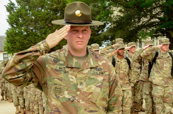 Army Staff Sgt. Joseph D. Moore salutes while in formation.