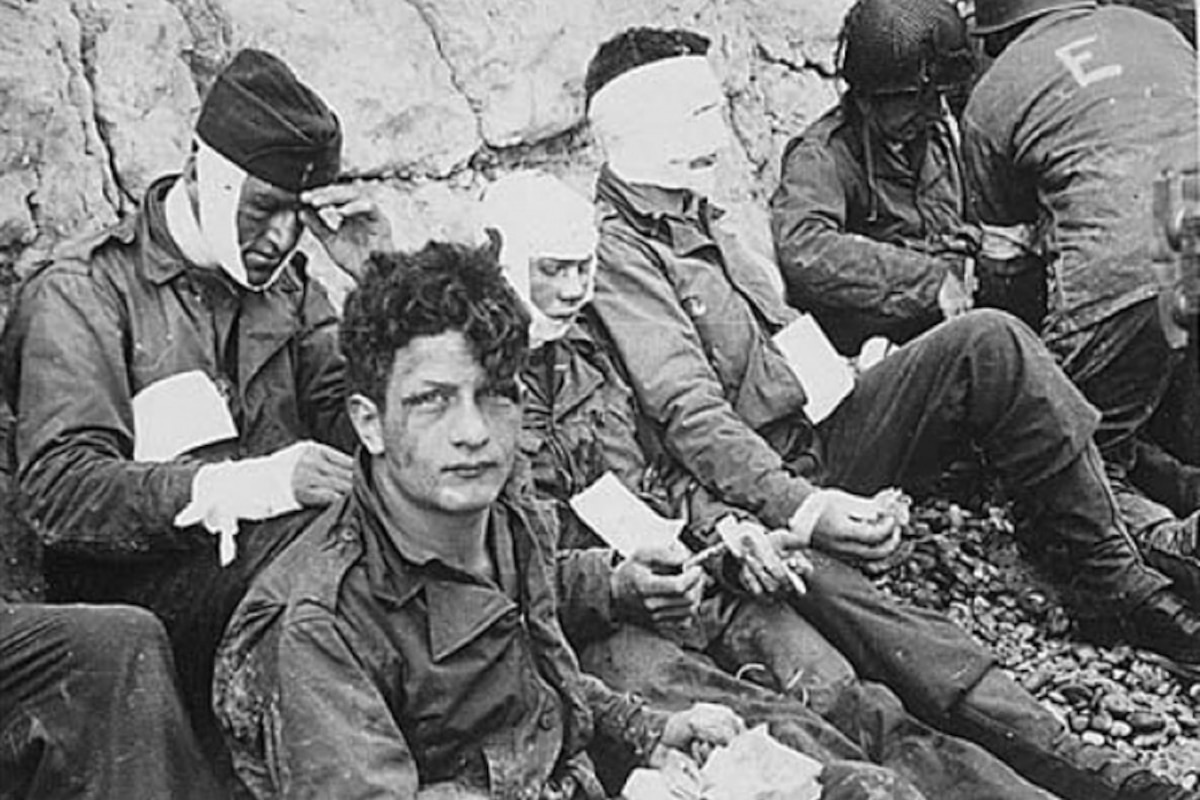 Wounded soldiers sit on a beach.