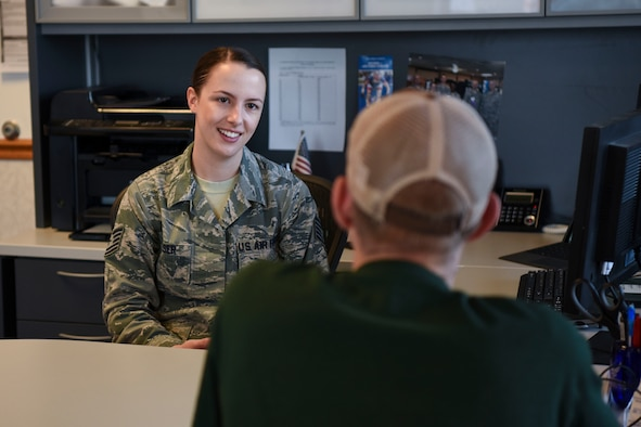 Air Force Tech. Sgt. Kimberly Reeser, recruiter located in Grand Forks, North Dakota, assists a recruit with the transition into the military here. Reeser said she feels a sense of accomplishment helping people become eligible to join the military. (U.S. Air Force photo by Airman 1st Class Melody K. Wolff)