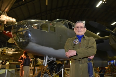 Picture of veteran in a flight suit standing in front of a B-25.
