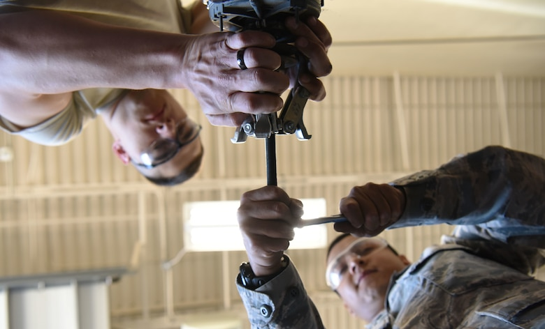 Senior Airman Julian Hernandez, a 28th Civil Engineer Squadron heating, ventilation and air conditioning journeyman, and Airman 1st Class Michael Schall, a 28th CES HVAC apprentice, use a vice grip and a wrench to fix a fan motor at Ellsworth Air Force Base, S.D., May 3, 2018. The 28th CES HVAC shop is responsible for installing and maintaining all of Ellsworth's heating, cooling, ventilation and refrigeration equipment. (U.S. Air Force photo by Airman 1st Class Thomas Karol)