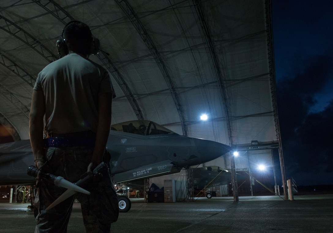 U.S. Air Force Senior Airman Daniel Portilla-Romero, 33rd Aircraft Maintenance Squadron crew chief, stands near an F-35A Lightning II as they await permission to taxi May 30, 2018, at Eglin Air Force Base, Fla. The 33 FW conducted F-35A night flying operations May 29-31, 2018, satisfying a training requirement for student pilots who will routinely fly day and night operations upon entering the combat Air Force. During this iteration of the pilot training syllabus, the night flying portion was stretched later into evening hours than in the past, allowing for more qualifications to be checked off across fewer days. (U.S. Air Force photo by Staff Sgt. Peter Thompson)