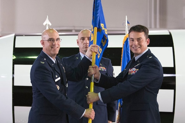 Col. Steven Lang, commander of the 45th Launch Group presents Lt. Col. Waylon Mitchell, commander of the 45th Launch Support Squadron and the 5th Space Launch Squadron, with the 45th LCSS guidon May 31, 2018 at Cape Canaveral Air Force Station, Fla. Mitchell assumed command from Lt. Col. Kathryn Cantu, and took on the role of dual-hatted commander. (U.S. Air Force photo by Airman 1st Class Zoe Thacker)