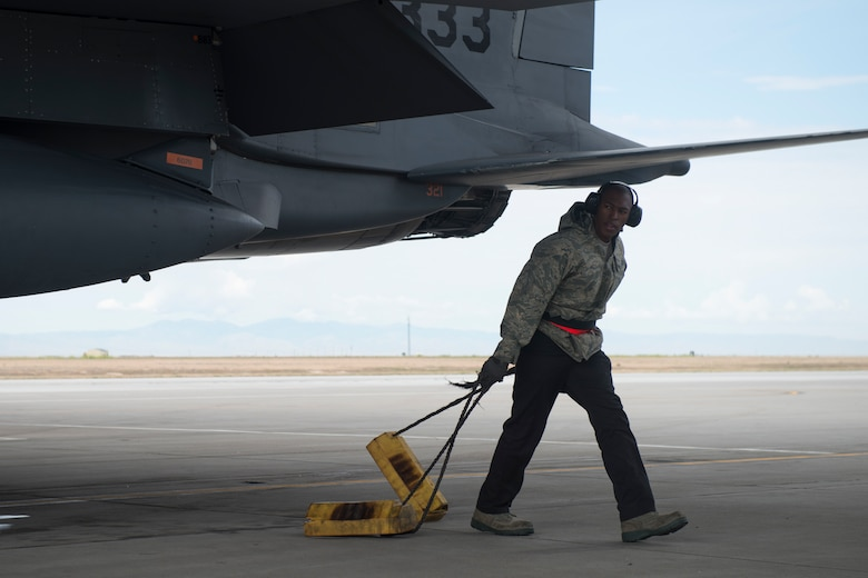 Airman 1st Class Dexter Holiday, 366th Aircraft Maintenance Squadron weapons load crew member, pulls the chocks from an F-15E Strike Eagle during an exercise, May 23, 2018 at Mountain home Air Force Base, Idaho. Gunfighter Flag 18-2 encompassed both the Belgian Air Component and Idaho Civil Air Patrol. (U.S. Air Force photo by Airman 1st Class JaNae Capuno)