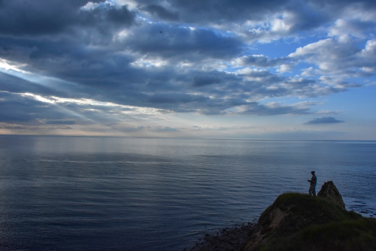 A soldier stands on a rocky promontory and looks out over a body of water below a low-lit, sun-streaked sky.