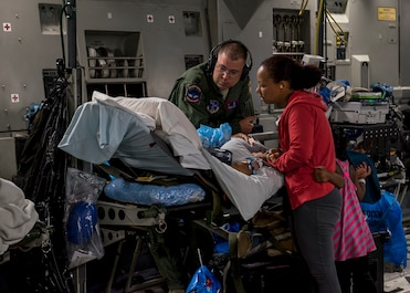 U.S. Air Force Capt. Thomas Hagan, a 123rd Medical Group critical care air transport team nurse, looks on as a patient is consoled by their family inside a C-17 Globemaster III flying over the Pacific Ocean from Travis Air Force Base, California, May 18, 2018. (U.S. Air Force photo by Lan Kim)