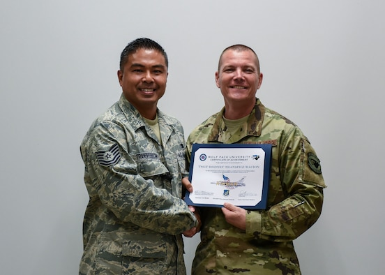 U.S. Air Force Tech. Sgt. Rodney Transfiguracion, 8th Maintenance Squadron unit deployment manager, receives a Wolf Pack University graduation certificate from Chief Master Sgt. Michael Moore, 8th Fighter Wing command chief, at Kunsan Air Base, Republic of Korea, Oct. 11, 2018. Wolf Pack University is a collegiate-mirrored system which includes a personalized curriculum, transcripts, advisors, electives and a diploma specific to being at Kunsan. (U.S. Air Force photo by Senior Airman Savannah L. Waters)