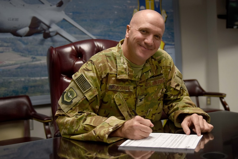 A man wearing the operational camouflage pattern uniform while writing on a piece of paper at a desk.