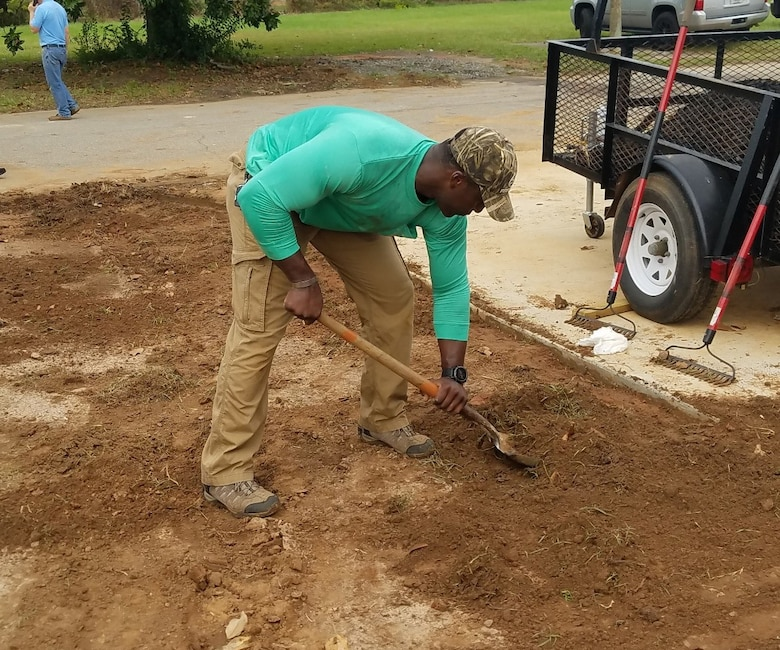 Capt. Michael Black, commander's executive officer for the 361st Intelligence, Surveillance and Reconnaissance Group, prepares the groundwork to lay sod on a project with Habitat for Humanity.