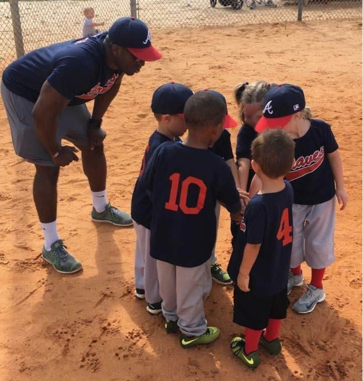 Capt. Michael Black, commander's executive officer for the 361st Intelligence, Surveillance and Reconnaissance Group, joins his youth t-ball team, he and his wife coach, in a pre-game huddle.