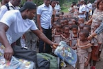 Spc. Dennis Duku hands out backpacks to school children at the Dadwen Schools Complex in western Ghana, which he attended years ago.