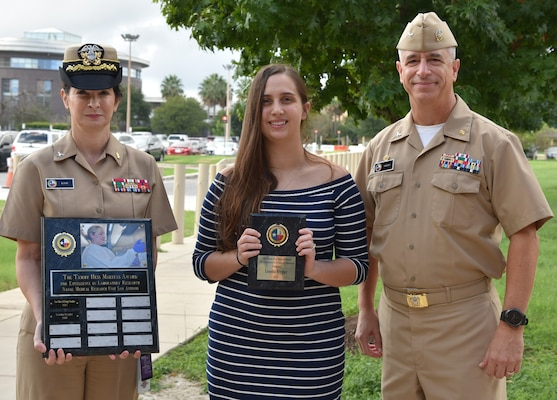 Capt. Michele Kane (left) , Naval Medical Research Unit San Antonio executive officer, and Capt. Thomas Herzig (right), NAMRU-SA commanding officer, present Leasha Stygler (center),with the Tammy Hess Maestas award for Excellence in Laboratory Research.