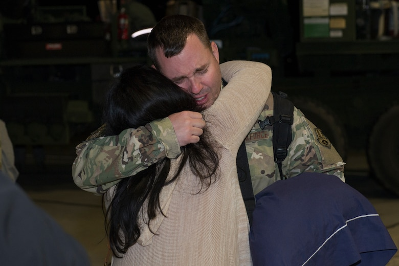 An Airman from the 726th Air Control Squadron returns from deployment and embraces his spouse, October 27, 2018, at Mountain Home Air Force Base, Idaho. over 100 Airmen from the 726th ACS deployed with mission of supporting communication between air craft and ground units. (U.S. Air Force photo by Senior Airman Tyrell Hall)