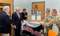 Maj. Gen. James Hoyer, Adjutant General of the West Virginia National Guard unveils a shodow box memorial plaque for brothers Phillip and Claude Gaujot and their wives honoring their great uncles Antoine and Julien Gaujot, Nov. 1, 2018, at the Logan/Mingo Readiness Center in Omar, West Virginia. The West Virginia National Guard armory was dedicated in honor of the brothers , both Congressional Medal of Honor recipients and former Soldiers who served in the late 1800's and early 1900's. (West Virginia National Guard photo by Bo Wriston)