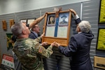 Maj. Gen. James Hoyer, Adjutant General of the West Virginia National Guard assists brothers Phillip and Claude Gaujot  in hanging a dedication plaque in honor of their great uncles Antoine and Julien Gaujot, Nov. 1, 2018, at the Logan/Mingo Readiness Center in Omar, West Virginia. The West Virginia National Guard armory was dedicated in honor of the brothers , both Congressional Medal of Honor recipients and former Soldiers who served in the late 1800's and early 1900's. (West Virginia National Guard photo by Bo Wriston)