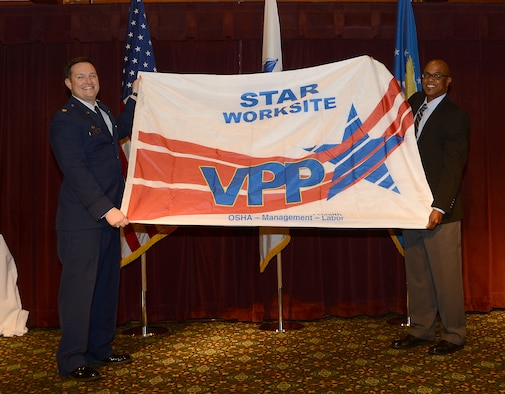 Lt. Col. Gregory Durham, 627th Logistics Readiness Squadron commander, and Darrell McKinney, 404th Army Field Support Brigade material readiness division chief, show the Voluntary Protection Program (VPP) Star Site flag to the audience Nov. 1, 2018 at Joint Base Lewis-McChord, Wash.