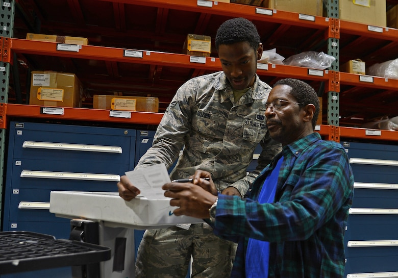 Airman 1st Class Joshua Dozier and Ronald Hines, 627th Logistics Readiness Squadron supply technicians, reviews a document before pulling an item off the warehouse shelf Oct. 19, 2018 at Joint Base Lewis-McChord, Wash.