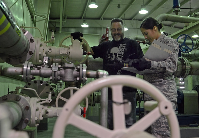 Airman 1st Class Kelsey Villegas, 627th Logistics Readiness Squadron fuels apprentice, and Gary Lam, 627th LRS fuels supervisor, inspects one of many fuel valves Oct. 19, 2018 at Joint Base Lewis-McChord, Wash.
