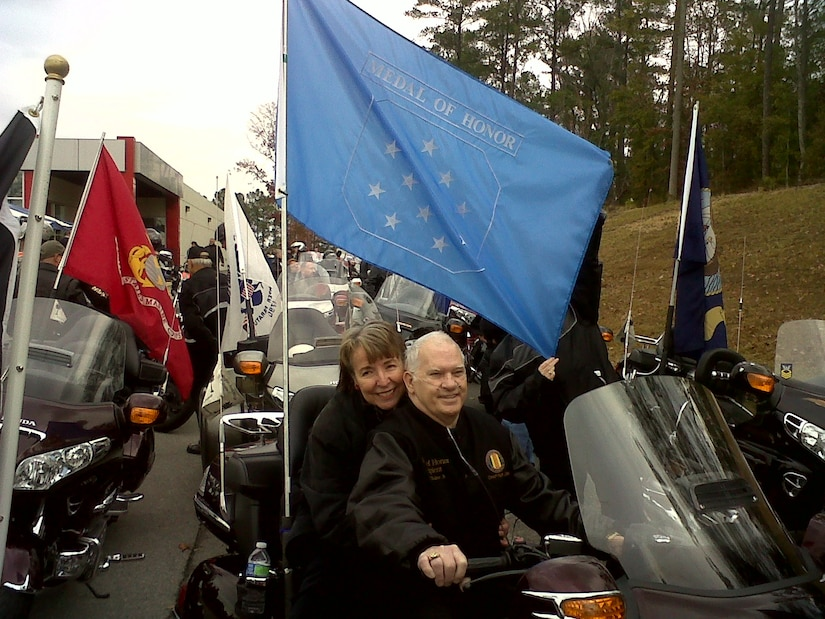 Baker and wife sit on motorcycle surrounded by other motorcycles.