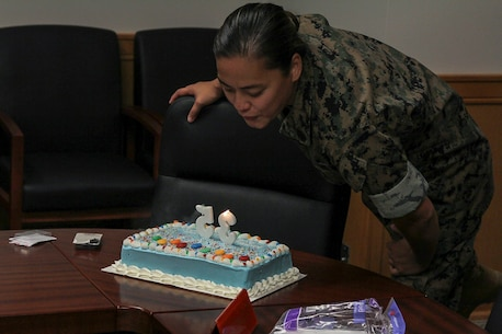Gunnery Sgt. Tiffany A. Freeman, U.S. Marine Corps Forces Korea personnel chief, blows out candles during the command's celebration of her birthday, here.  The Marines of MARFORK G-1 surprised Freeman with the birthday cake and the recognition of the entire staff. (Official U.S. Marine Corps photo by Capt. John Parry/ Released)