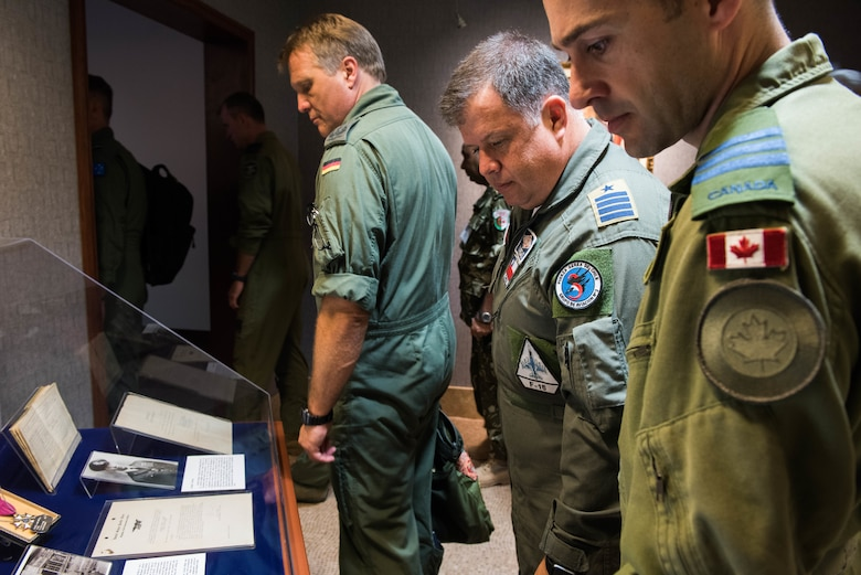 Foreign attaché members look at historical Pacific Air Forces (PACAF) photos and artifacts before entering the Kenney Conference Room at Headquarters PACAF during a tour of Joint Base Pearl Harbor-Hickam, Hawaii, Oct. 23, 2018.