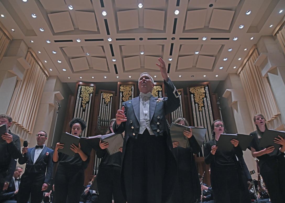 Col. Larry H. Lang, U.S. Air Force Band commander and conductor, invites the crowd to sing along with the band and Baylor University choir students at Baylor University in Waco, Texas, Oct. 24, 2018. On Lang's final trip before retirement, the band toured 12 locations in New Mexico and Texas, including Lang's hometown of El Paso, Texas. (U.S. Air Force photo by Senior Airman Abby L. Richardson)