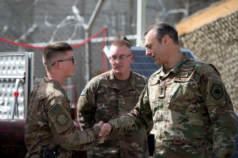 Lt. Gen. Joseph Guastella, commander of U.S. Air Forces Central Command, coins Senior Airman Aaron Thalmann, a quick response force Airman assigned to the 455th Expeditionary Security Forces Squadron at Bagram Airfield, Afghanistan, Oct. 29, 2018.