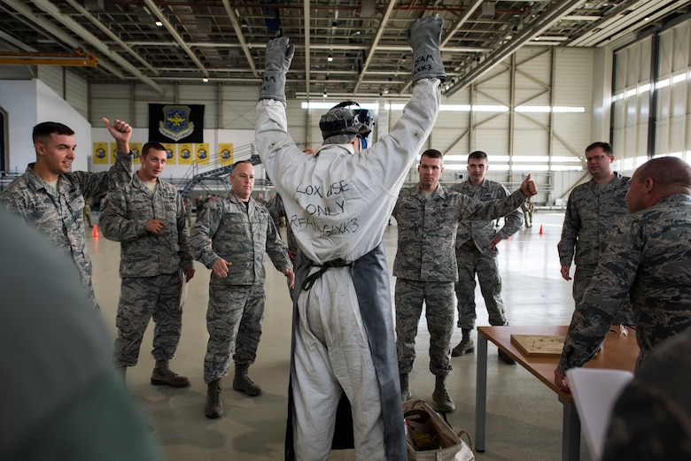 A U.S. Airman assigned to the 721st Aircraft Maintenance Squadron puts his hands up as fellow Airmen verify he is wearing all the correct liquid oxygen protective equipment as part of the maintenance relay during the 721st Air Mobility Operations Group safety down day on Ramstein Air Base, Germany, Oct. 19, 2018. The suit is used daily by members to service aircraft liquid oxygen systems. In addition to the relay, physical fitness, resilience and other wingman concepts were all included in the safety down day. (U.S. Air Force photo by Senior Airman Devin M. Rumbaugh)