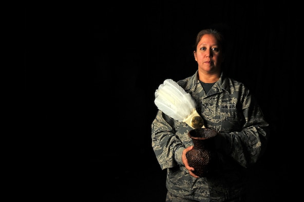 Master Sgt. Serena Dedes, an equipment manager at the 180th Fighter Wing, Ohio Air National Guard, holds a traditional feather flag during Pow Wows along with water vase handmade by her mother. Pow Wows are Native American ceremonies involving feasting, singing and dancing. November is dedicated to honoring Native American Indian Heritage and the 180FW and U.S. Air Force value the uniqueness our diverse service members bring to the mission. Air National Guard photo by Airman First Class Hope Geiger.