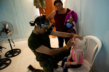 Mexican Army Maj. Didier Escobar, an optometrist, gives an eye exam to a young patient at one of two medical sites.