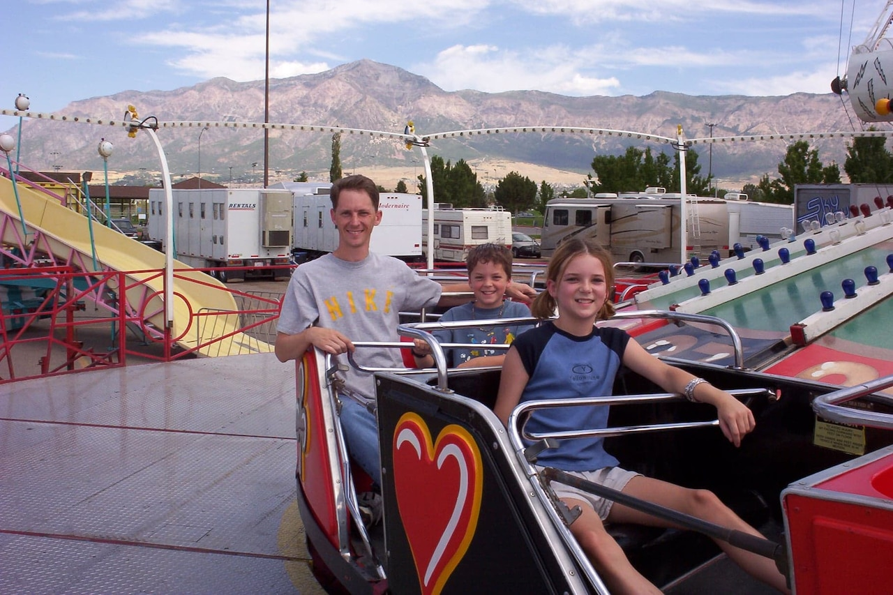 Three people enjoy an amusement park ride.