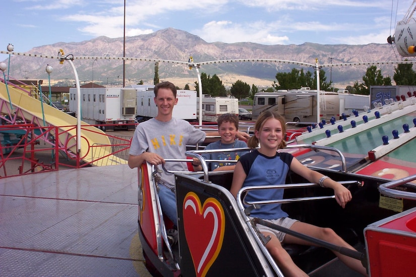 Three people enjoy an amusement park ride.