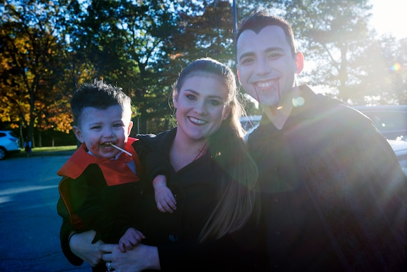 U.S. Air Force Capt. Manuel Medina, a KC-135 pilot with the 64th Air Refueling Squadron, poses with his wife and son during the Airmen and Family Readiness Trunk-or-Treat event Oct. 26, 2018, at Pease Air National Guard Base, N.H. More than 20 service members and their families decorated their car trunks with games, candy and other treats for everyone to enjoy. (Photo by Airman 1st Class Victoria Nelson, 157th ARW Public Affairs)