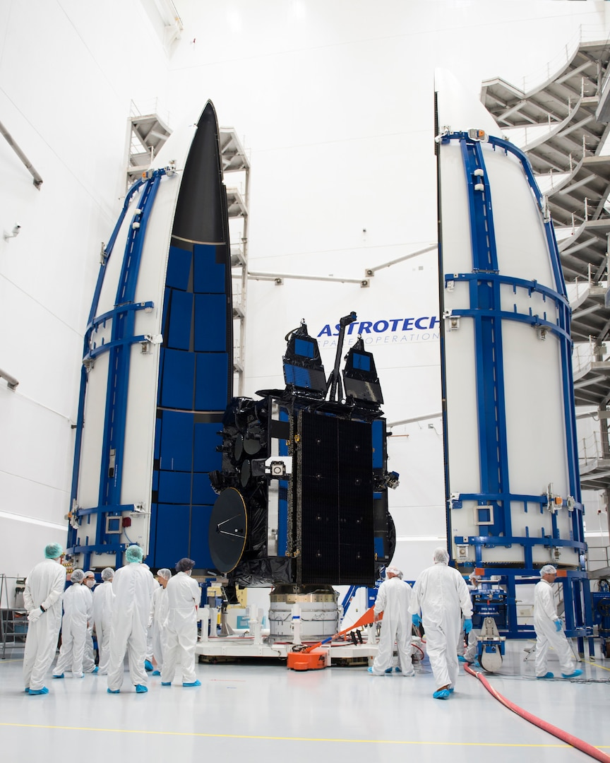 Satellite about to be enclosed in between to large white panels, in a white room surrounded by people wearing white coveralls.
