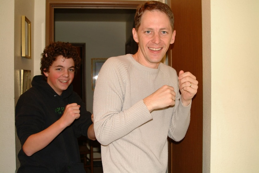 Two men pose for a picture with clenched fists.