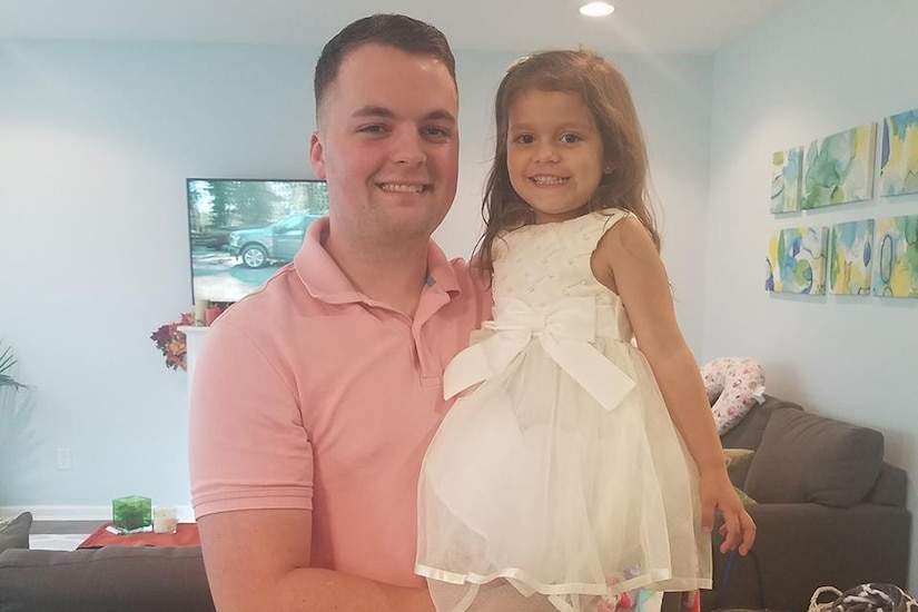 A father poses with his daughter in his arms.